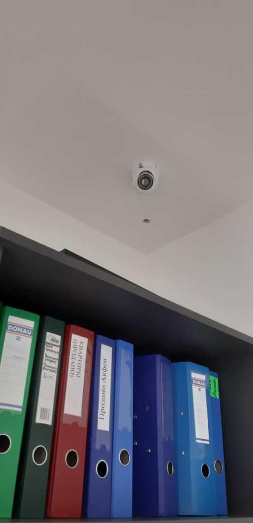 Камера наблюдения на потолке в углу комнаты